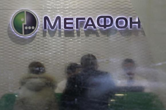 Customers and staff are seen through the partially cleaned window of a Megafon shop in Moscow
